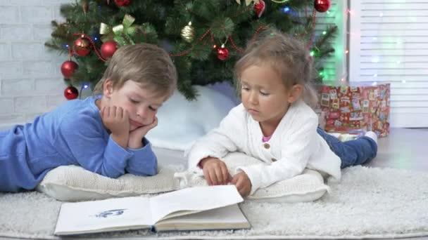 Dvě malé roztomilé sourozenci čtení knihy na podlahu u vánočního stromu