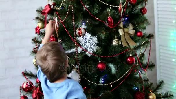 zwei kleine Kinder Bruder und Schwester schmücken tagsüber den Weihnachtsbaum