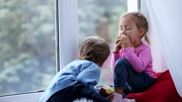 Bátyja és húga ül ablakpárkányon, étkezési alma és néz ki az ablak.