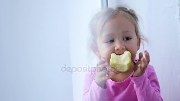 Vicces, aranyos kislány ül az ablakpárkányon, és étkezési Alma portréja