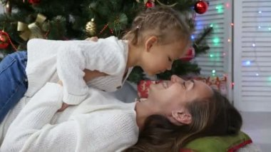 Cute little girl having fun and kissing her mom next to Christmas tree