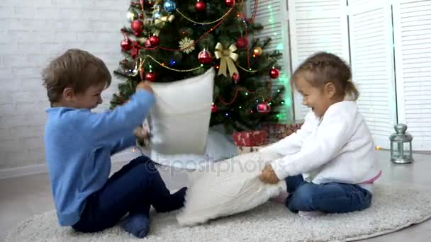 Playful siblings fighting with pillows at home next to Christmas tree.
