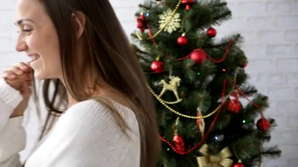 Young mother turns her little daughter with Christmas tree on the background