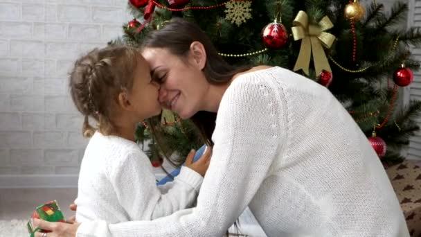 Mladí docela matka s darem pole v ruce objetí a polibky její malá dcerka