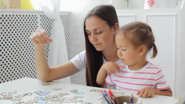 Mother and daughter doing a puzzle together in the light living room