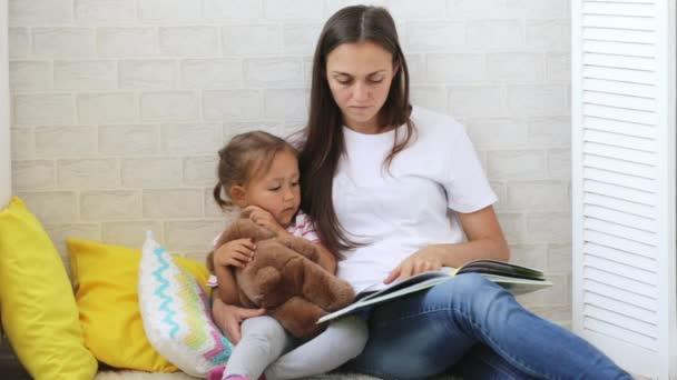 Libro di lettura di giovane madre per la sua piccola figlia