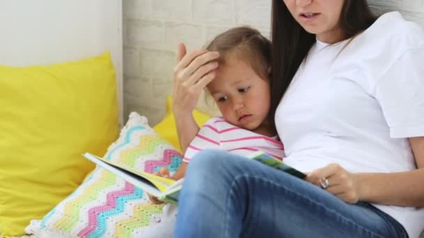 Mladá matka čítanka pro svou malou dceru.