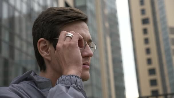 Engineer in uniform removes glasses with building on the background.