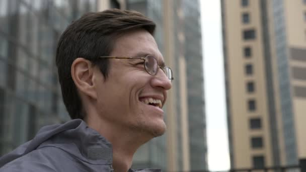 Worker in uniform laughing and removing googles with building on the background