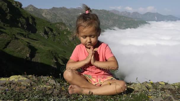 kleines süßes Mädchen meditiert auf dem Gipfel des Berges