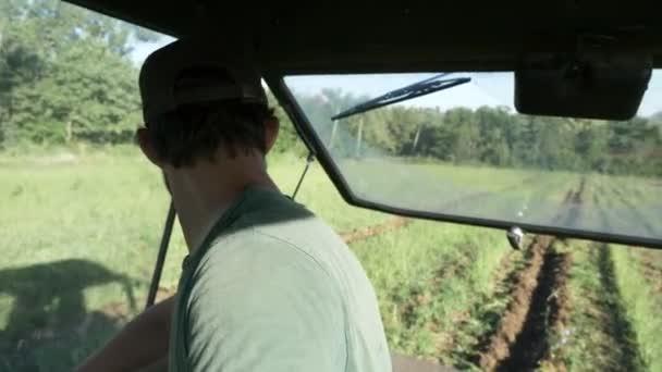 Farmer driving tractor on the potato field in potato harvesting process