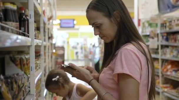 Žena s malou dcerou v nákupní košík výběru omáčka v supermarketu
