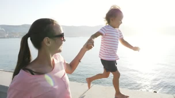 Young mother with little daughter running holding hands, smiling and laughing