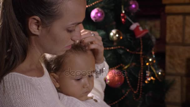 Mutter mit kleiner Tochter liest Buch am Kamin und Weihnachtsbaum