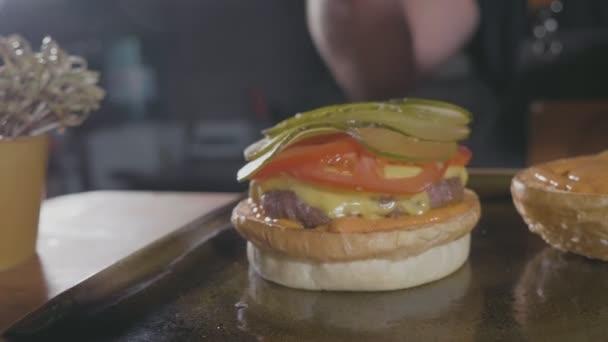Close-up shot z rukou kuchaři připravují hamburger hovězí karbanátek se sýrem