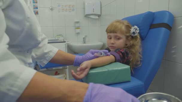 Nurse is taking blood sample from a vein in the arm of little girl