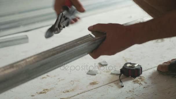 Hände von Männern schneiden Rahmen für Montage Trockenbau in unfertigen Wohnungen