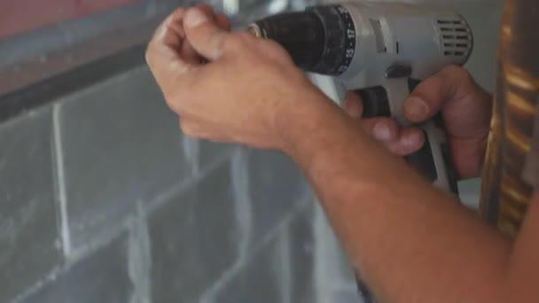 Pracovník provádět instalace sádrokartonu a pomocí šroubováku a šroub pro práci, closeup