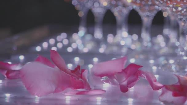 Pyramide aus Gläsern mit Champagner und fallenden Blütenblättern
