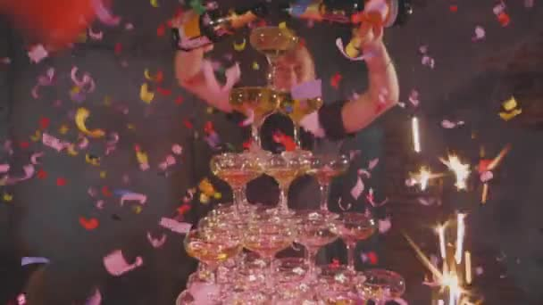 Waiter pouring champagne in glasses at pyramid with confetti and fountains