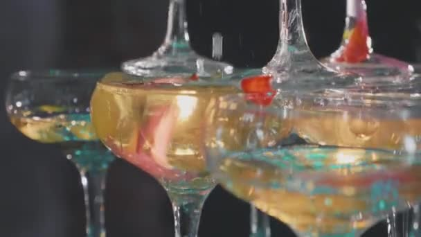 Číšník nalil šampaňské v brýlích na pyramidu v pomalém pohybu, detail