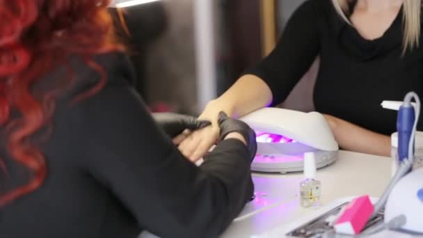 Redhead master doing massage her female blonde client after manicure procedure