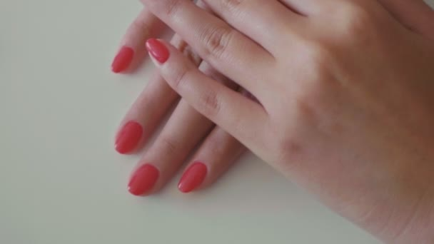 Hände mit frischer roter Maniküre im Nagelstudio