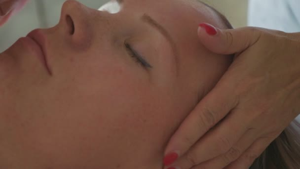 Cosmetologist is cleaning womans face by cotton sponge at spa salon