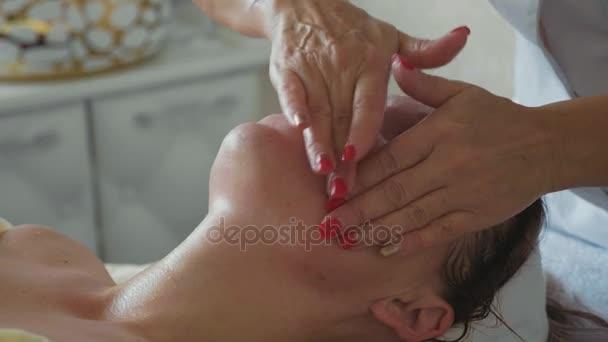Schöne junge Frau entspannend mit Gesichtsmassage im Luxus-Spa-Salon, Nahaufnahme