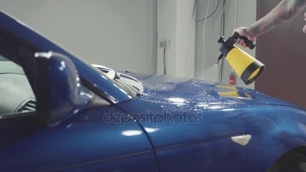 Zblízka mistra leštění tmavě modré auto v dílně, pomalý pohyb
