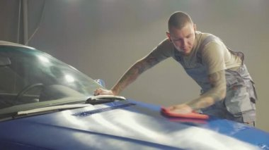 Master finish polish the half hood of deep blue car and wiping the hood