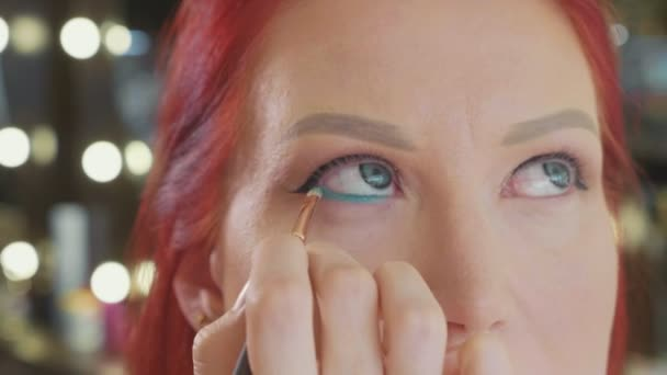 Make-up artist applying makeup to models eye. Close up view.