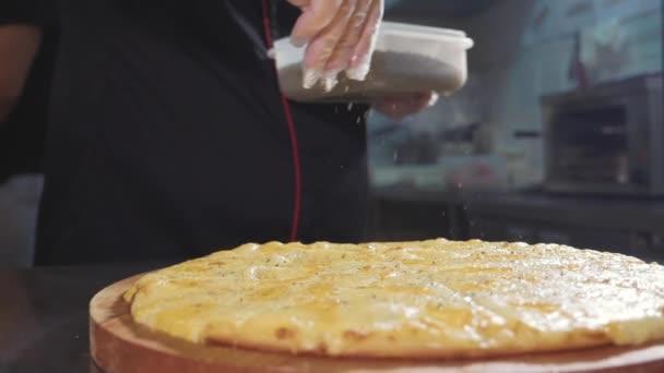 Detail kuchař odlévání koření na pizzu v pomalém pohybu