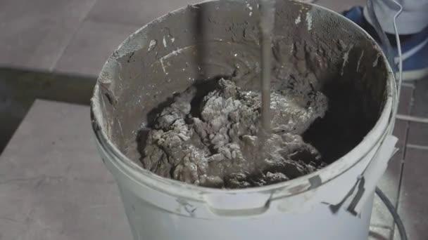 Close-up mischen Beton in Eimer über Bohrmaschine auf Baustelle