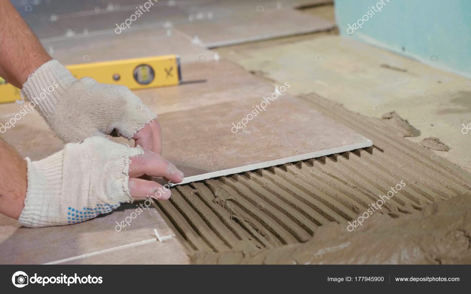 Tegels Over Tegels : Professionele werker tegels op de vloer te leggen u stockfoto