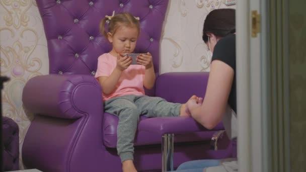 Roztomilá holčička pomocí chytrého telefonu v proceduře pedikúra v salonu beauty spa