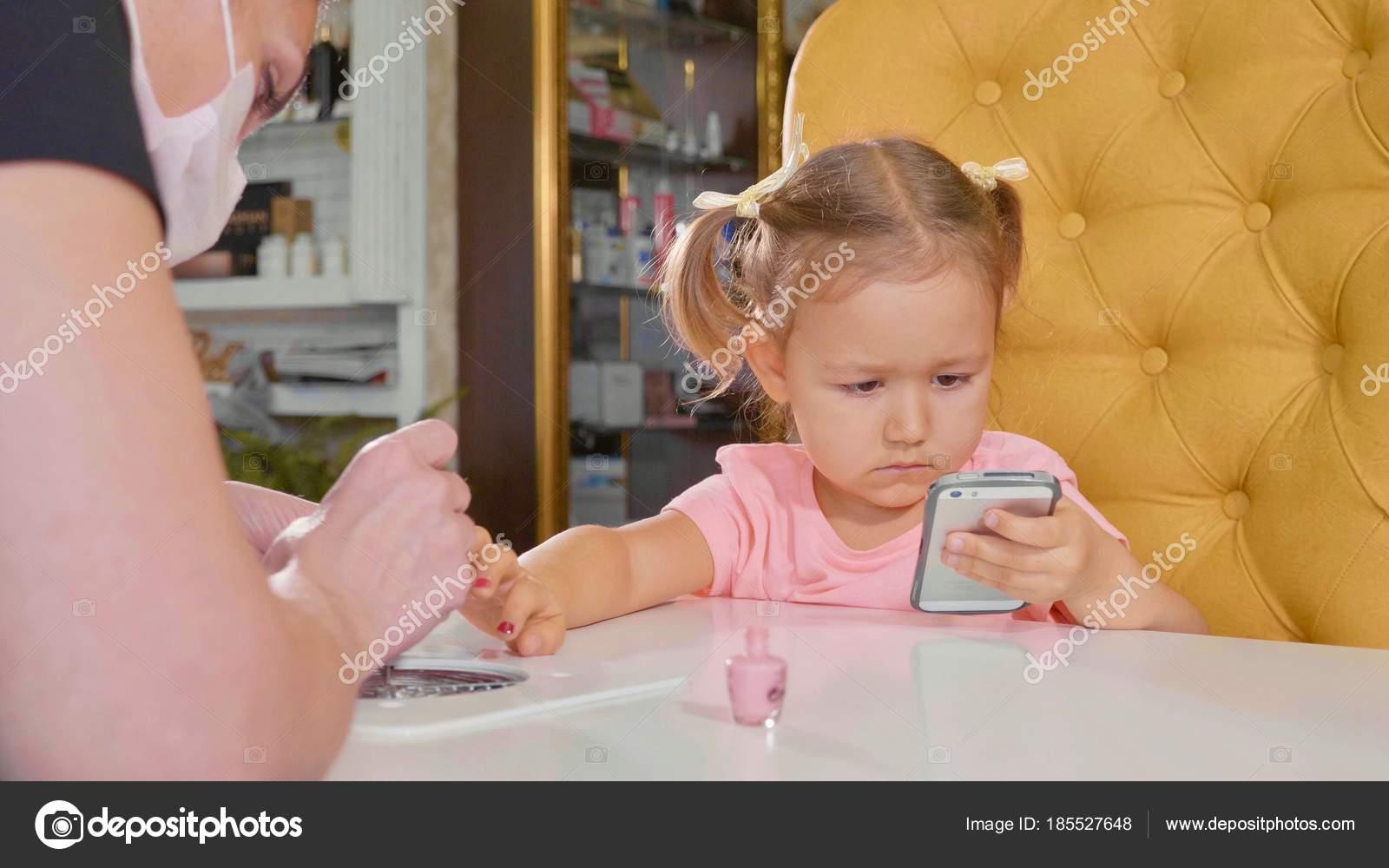 Beautician applying nail polish to kids nail in a nail salon ...