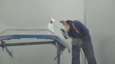 Auto painter spraying white paint on car front bumper in special booth
