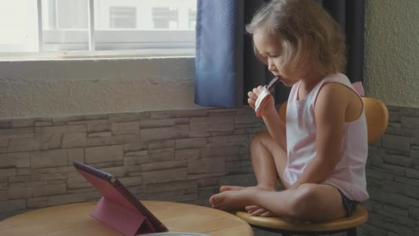 Little cute child girl watching something in the tablet and eats fruit bar
