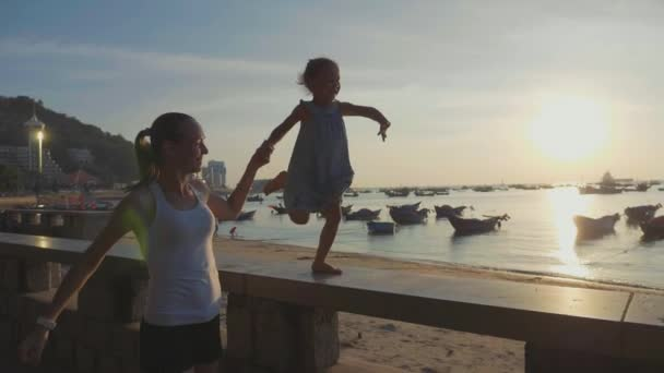 Young mother with little daughter runs at seafront in slow motion.