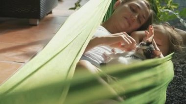 Happy mother and daughter relaxing together in a hammock at garden in summer day