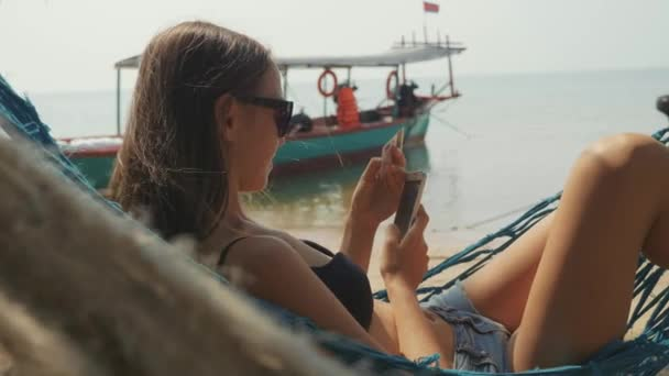 Young woman lying on hammock with smart phone and bank card at the sandy beach
