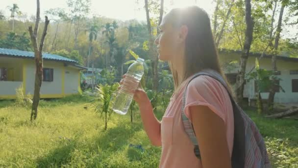 Young woman stand on countryside path in asian village and drinking water.
