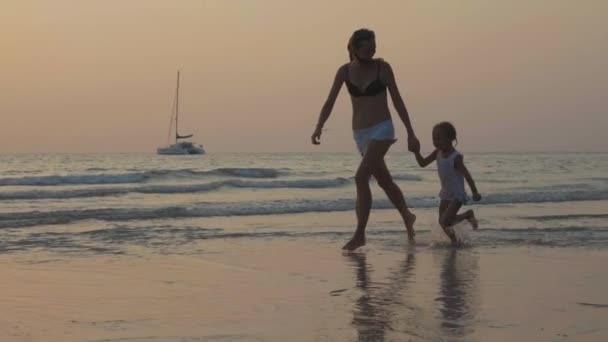 Silhouetteother with little daughter running on sea shore with holding hands.