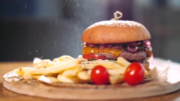 Křupavé hranolky s hamburgerem na dřevěné desce. Koncept rychlého občerstvení.
