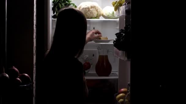 Žena otevírá ledničku, v noci si vezme sladký dezert a svačinku