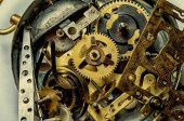 A retro clock from the past disassembled into gears. Tweezers mechanic in the foreground