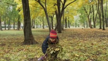 Little girl throws up an armful of autumn leaves.