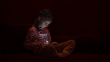 Little girl with a smartphone is sitting on sofa.