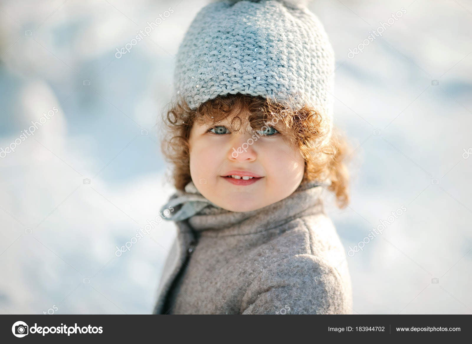 Portrait of cute smiling little girl with short curly hair in woolen hat  and winter coat — Photo by volkovich a dfef9f7e5f9